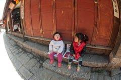 Meisjes het zitten en geluk in de Oude stad van Lijiang Dayan. Stock Afbeeldingen
