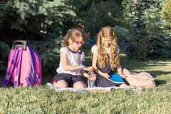 Meisjes 7, 8 jaar oud in schooluniformen met rugzakken met boeken en waterflessen die in park zitten stock fotografie