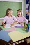 Meisjes in klaslokaal dat schoolwork, het schrijven doet stock fotografie