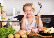 Meisjes kokende soep met gietlepel Stock Fotografie