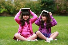 Meisjes met boeken op hoofd Stock Foto's