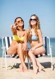 Meisjes met dranken op de ligstoelen stock foto's