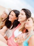 Meisjes met dranken op het strand stock fotografie