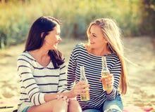 Meisjes met dranken op het strand stock foto