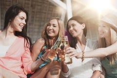 Meisjes met dranken op het strand stock foto's