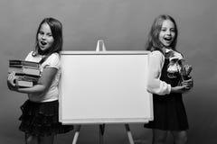 Meisjes met gelukkige gezichten en kantoorbehoeften Schoolmeisjes naast whiteboard op groene achtergrond Royalty-vrije Stock Afbeelding