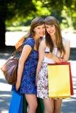 Meisjes met het winkelen zakken stock foto