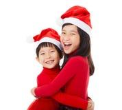 meisjes met Kerstmis hoed en het Geven van Een andere Omhelzing Royalty-vrije Stock Fotografie