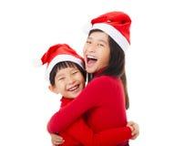 meisjes met Kerstmis hoed en het Geven van Een andere Omhelzing Stock Foto