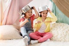 Meisjes met keukengerei het spelen in tent thuis stock afbeeldingen