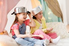 Meisjes met keukengerei het spelen in tent thuis stock afbeelding