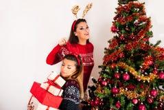 Meisjes met rendierhoornen op hand en vele giftdozen en Kerstboom stock foto's