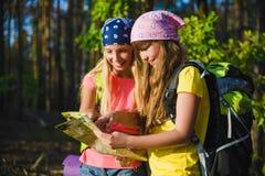 Meisjes met rugzak Looing bij kaart Avontuur, reis, toerismeconcept royalty-vrije stock fotografie