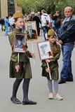Meisjes in militaire eenvormige greepportretten van hun verwanten in het actie` Onsterfelijke regiment ` op Overwinningsdag in Vo royalty-vrije stock foto