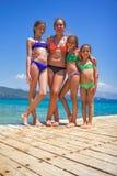 Meisjes op de houten pijler op het overzees stock foto