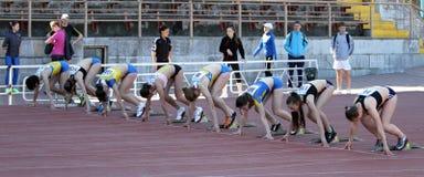 Meisjes op het begin van de 100 meters ras Stock Afbeelding