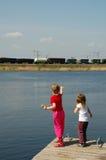 Meisjes op pijler en trein Stock Foto's
