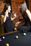 Meisjes op telefoon in poolroom   Royalty-vrije Stock Afbeeldingen