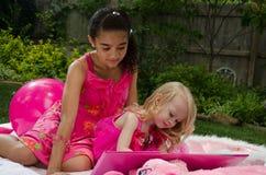 Meisjes in openlucht met een boek Stock Fotografie