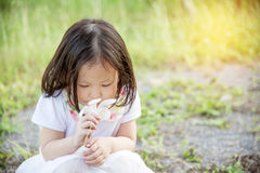 Meisjes ruikende bloem in park stock foto's