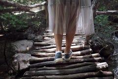Meisjes` s benen met rugzak die over het hangen van brug in tropisch bos lopen Royalty-vrije Stock Afbeelding