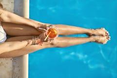 Meisjes` s benen over zwembad in openlucht Royalty-vrije Stock Afbeeldingen