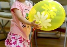 Meisjes` s handen die een gele ballon voor verjaardagsgift houden royalty-vrije stock foto