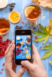Meisjes` s handen met telefoon, foto'ssamenstelling met thee en fruit Stock Fotografie