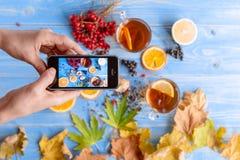 Meisjes` s handen met telefoon, foto'ssamenstelling met thee en fruit Stock Foto's