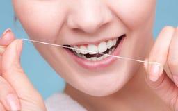 Meisjes schoonmakende tanden met tandzijde Vertragingen en wapens royalty-vrije stock afbeelding