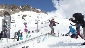 Meisjes snowboarder dia op ijzersleep Karton kosmische voorwerpen cameraman stock videobeelden