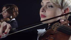 Meisjes in spel de violen in een samenstelling in een ruimte Zwarte achtergrond Sluit omhoog stock video