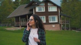 Meisjes sprekende telefoon in het groene platteland stock footage