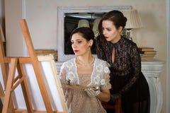 Meisjes in uitstekende kleding in de olieverfschilderijklasse Voegde een kleine korrel, imitatie van filmfotografie toe royalty-vrije stock foto