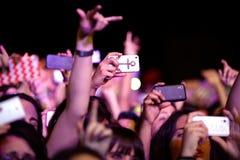 Meisjes van het publiek voor het stadium, die met hun smartphones registreren stock afbeeldingen