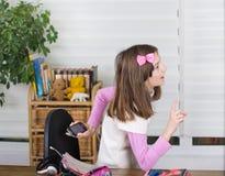 Meisjes verbergende telefoon Stock Afbeeldingen