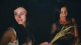 Meisjes verzamelde aartjes - de nacht op een gebied met kaarslantaarns stock videobeelden