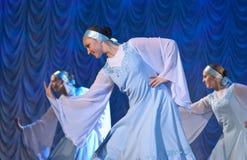 Meisjes in witte kleding die op stadium, Russische Nationale Dans dansen Stock Afbeelding