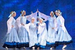 Meisjes in witte kleding die op stadium, Russische Nationale Dans dansen Stock Foto