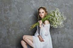 Meisjes witte lichte kleding en krullend haar, portret van vrouw met bloemen thuis dichtbij het venster, zuiverheid en onschuld K stock foto