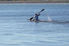 Meisjesatleet belast met canoeing op een waterkanaal stock foto