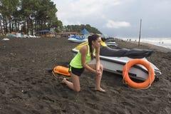 Meisjesbadmeester, met oranje boei voor het levensbesparing op plicht die overzees, oceaanstrand overzien Waterautoped op strand royalty-vrije stock foto