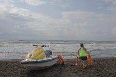 Meisjesbadmeester op plicht die een boei houden bij het strand Waterautoped, het materiaal oranje preserver van de badmeesterredd stock foto's