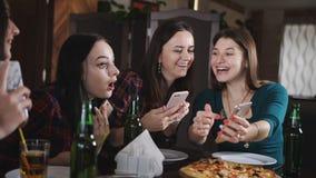 Meisjesbeelden van pizza op uw smartphone Het bedrijf van vrolijke meisjes in het restaurant Meisjes die pret het drinken hebben stock videobeelden