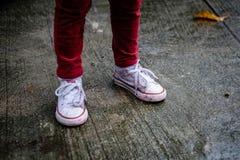 Meisjesbenen in rode broek, met schoenen nat en vuil met verf Royalty-vrije Stock Afbeelding