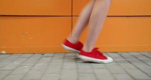 Meisjesbenen in rode trainers Looppas langs de oranje muur stock videobeelden
