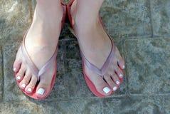 Meisjesbenen in rubber rode pantoffels op de stoep royalty-vrije stock afbeeldingen