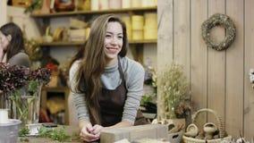 Meisjesbesprekingen met somebody in bloemwinkel, dan kijkt zij in de camera stock footage