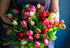 Meisjesbloemist die een boeket van tulpen houden stock afbeelding