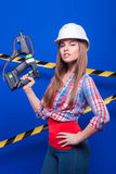 Meisjesbouwer in de bouwhelm en beschermende brillen met een bouwhulpmiddel op een blauwe achtergrond Royalty-vrije Stock Foto's